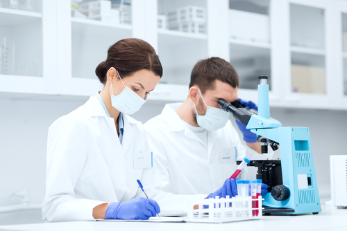 CRL male employee looking in microscope, CRL female employee taking notes