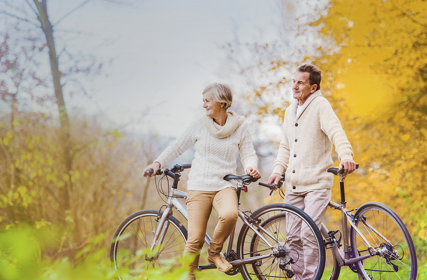 an older couple wearing matching sweaters on bikes on a trail